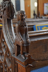 bench end: bearded man sitting on a square stool (19th Century)