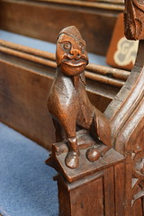 bench end: a unicorn turned into an ugly-faced man (15th Century recut 19th Century)