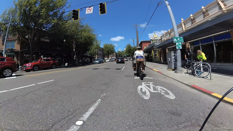 The road has pavement and a curb and only a bike sharrow marking.