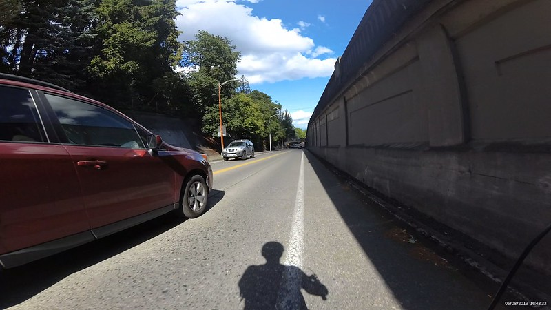 The bicyclists shadow falls partly into the car lane with a car passing to the left.