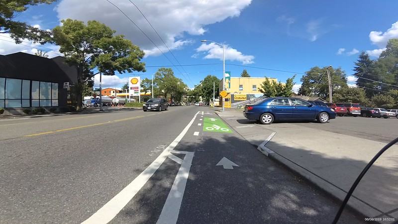 The protected bike lane ends and a car has just turned into the adjacent business in front of the cyclist.