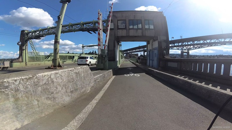 The green university bridge shows a wide opening for bikes and a separated space for pedestrians.