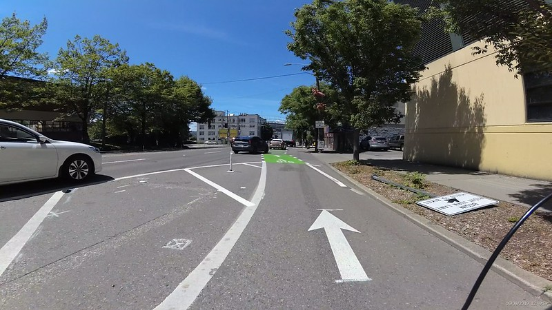 A white paint buffer on the left where cars would drive to the left before merging right into the bike lane.