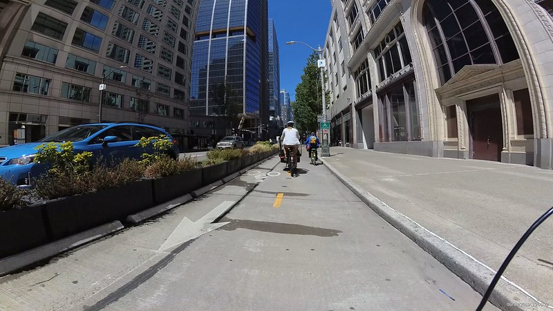 A black cargo bike is passing a slower bike, taking up the entire two lanes of bike route.
