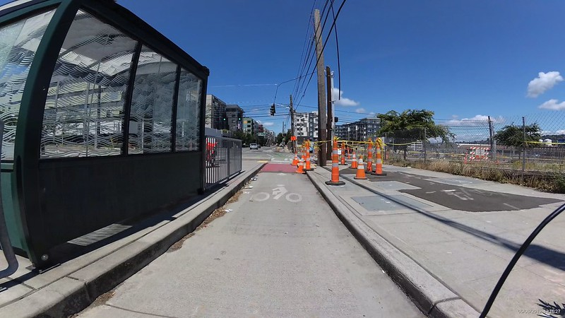 A bus stop shelter on the left and construction signs and roping obscures any sign of a bike lane going off to the east on Roy.