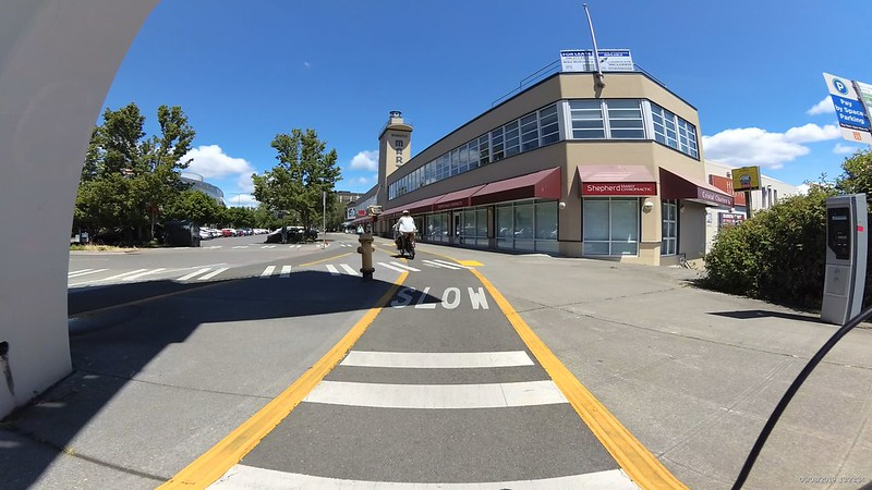 The Westlake Cycle track is separated from the sidewalk proper with yellow tactile strips. The shops of the marina are to the right.