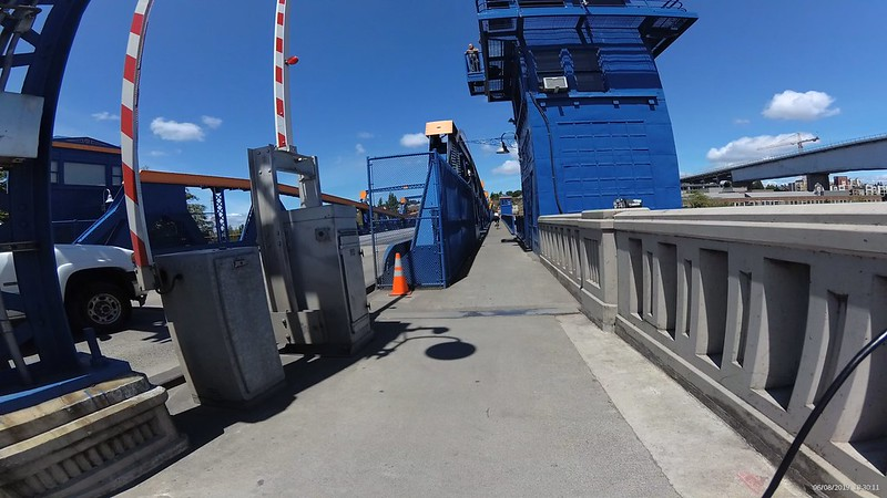 Entering the Fremont bridge pedestrian bike lane is very narrow with tall blue metal girders and panels.