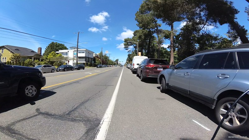 Cars are parked next to a curb but very close into the bike lane