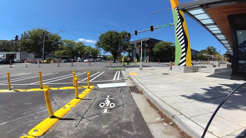Westbound at Dearborn Rainier are yellow curbs and flex posts for a diverter and green paint bike cross bikes going across the wide intersection.