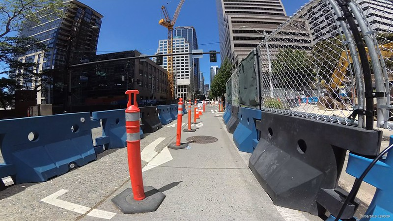 Construction detour has many tall orange cones to separate two bike lanes separated from car traffic with large solid portable dividers.