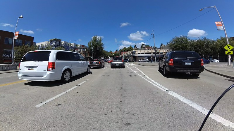Cars in front and two the right with a narrow strip of painted bike lane between a car and a curb.