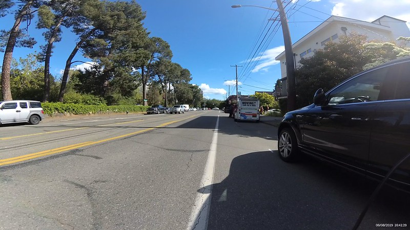 A truck parked with its door open which extends nearly across the entire bike lane.