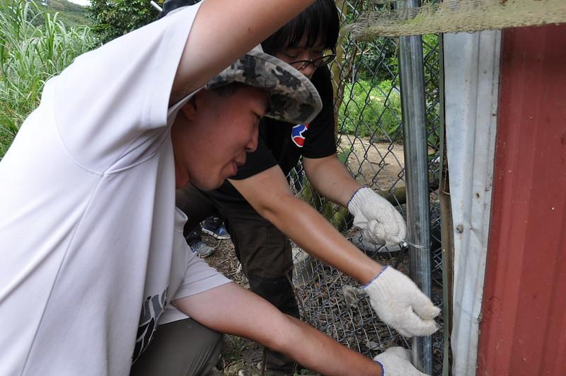 志工兩人一組,合作將菱形網與鐵柱綁好。孫文臨攝