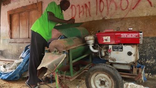 Kassim standing next to his 16-hpr maize shelling machine. Photo credit: Audifas Gasper/IITA.