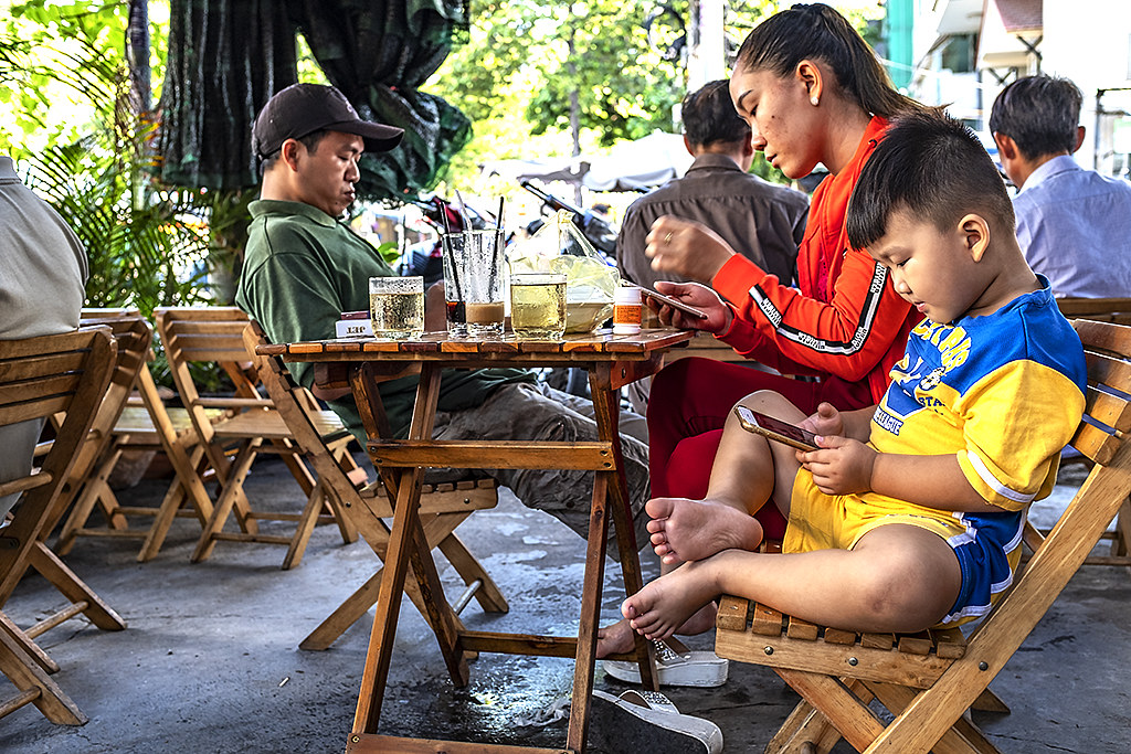 Couple with toddler in cafe, all looking at cellphones--Saigon