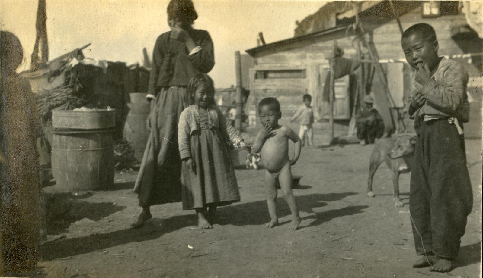 1918. Азиатские дети возле дома