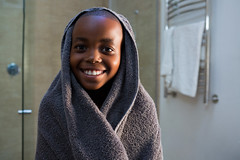 Portrait of smiling boy wrapped in gray towel