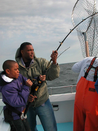 Photo of a man and his son hauling in a big catch