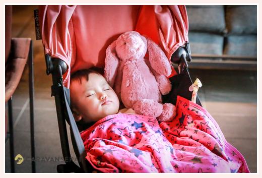 a baby girl sleeping on a stroller