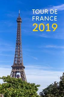 Tour de France 2019 Aufschrift für das berühmteste Fahrradrennen der Welt, neben dem Eiffelturm vor blauem Hintergrund