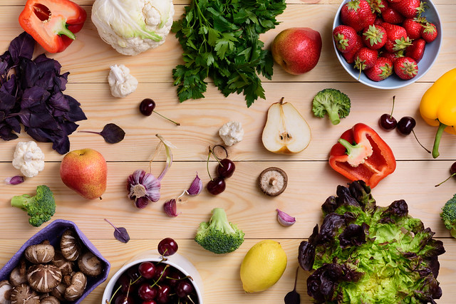 Variety of colorful fruits, vegetables and berries. Healthy diet concept. Vegetarian organic food set over wooden table. Top view.