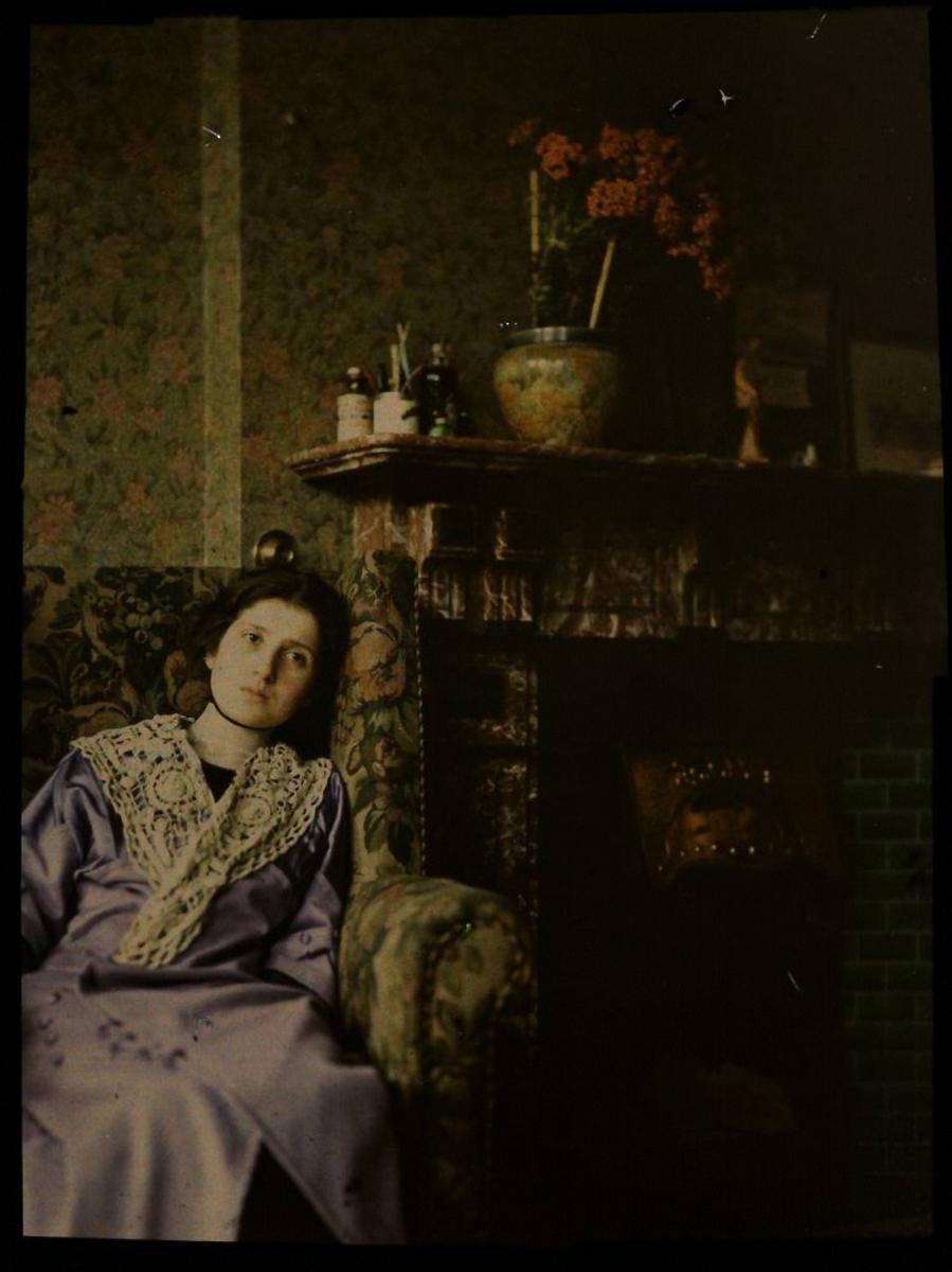 1915.  Женщина в голубом платье сидит возле камина