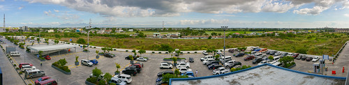 philippines landscapes southeast asia tropical country view rural suburban transition city homes residence buildings structures trees cell tower cellular horizon broad scenic wide angle panorama panoramic parking lot cars vehicles people walking mall