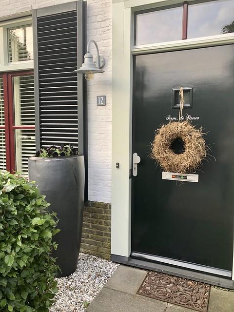 Hoge pot violen bij landelijke voordeur met krans
