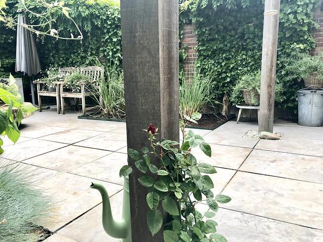 Stadstuin pergola tuinstoelen grote tuintegels