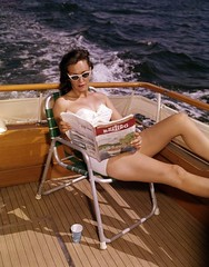 "Mrs. Charles Miller reading a copy of ""Motor Boating"" during a South Florida boat trip"