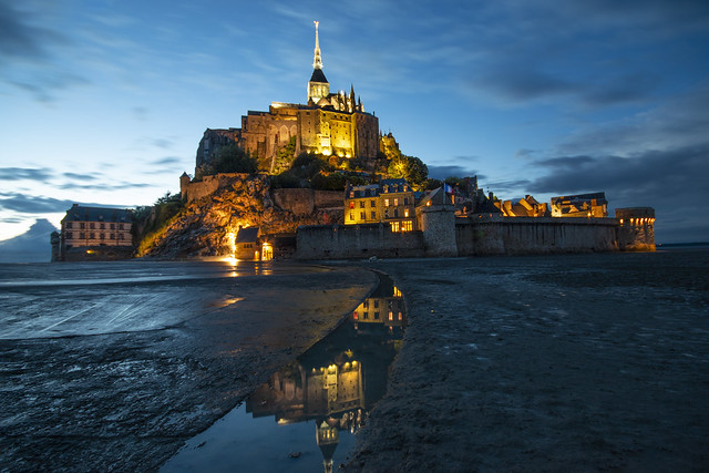 as night falls the magnificent Mont Saint Michel and its lights are reflected in the water channels. Manche, Normandie, France
