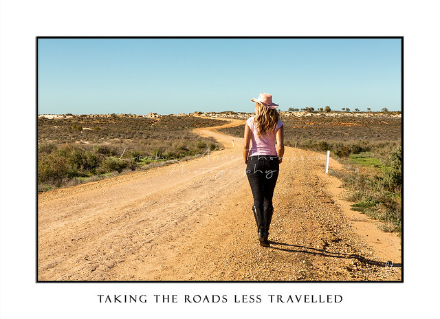 Woman walks a winding dirt road in outback Australia