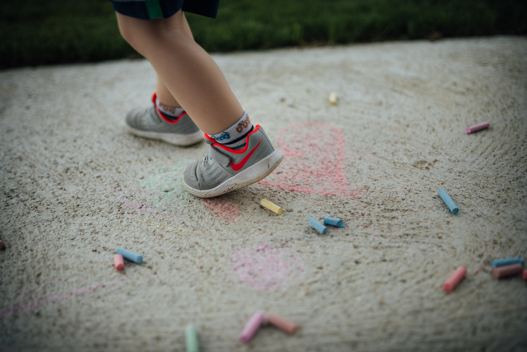A boy stepping on colored chalk