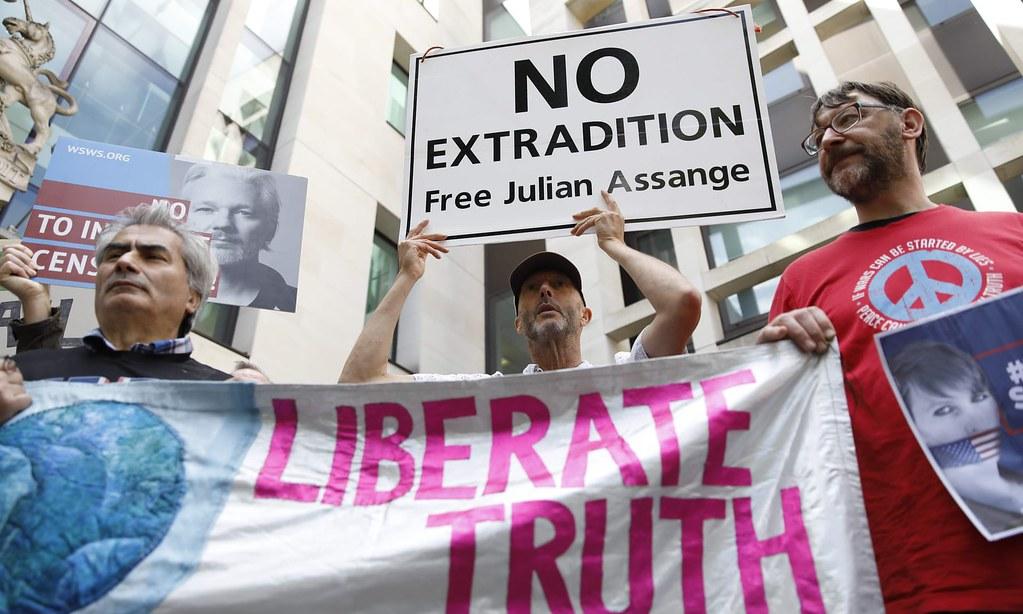 法院外阿桑奇的支持者高舉「拒絕引渡阿桑奇」的標語。(圖片來源:Tolga Akmen/AFP)