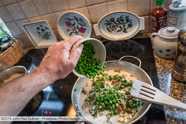 Adding peas to the pan with Morels and Ramps in White Wine Cream Sauce