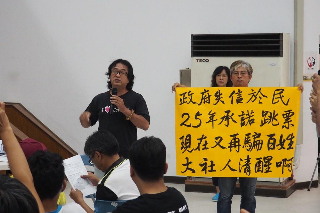 居民舉海報,要求政府不該違背25年前的承諾。攝影:李育琴