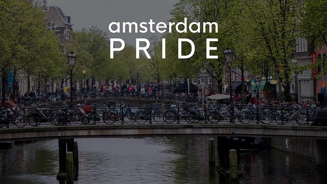 Touristen und Fahrräder auf niederländischen Brücken im Rotlichtviertel von Amsterdam, mit dem Bildtitel Amsterdam Pride