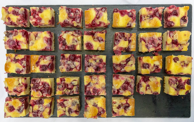 Flatlay of cherry-almond cake cut into pieces, on a black tray