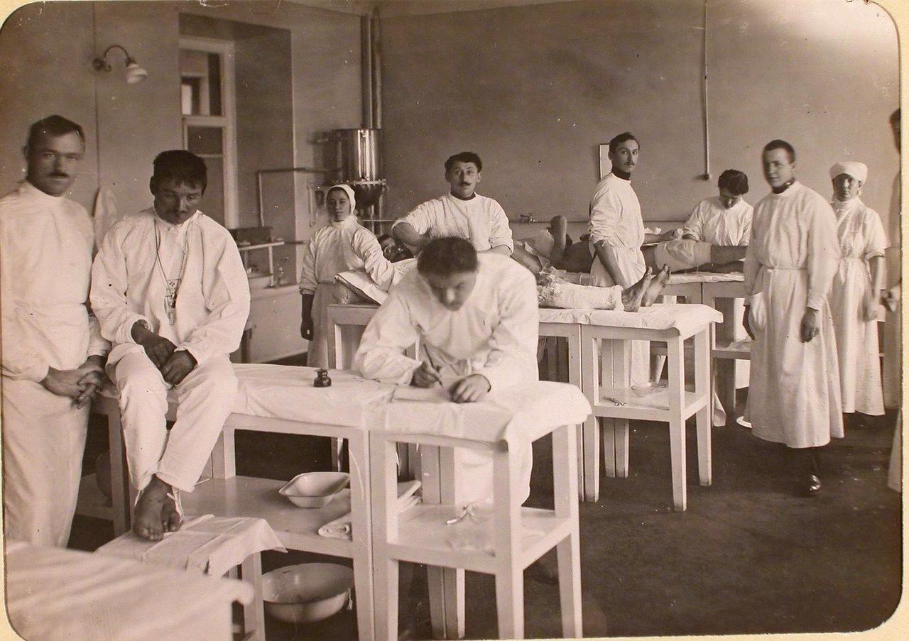 10. Медицинские сестры и братья милосердия делают перевязки раненым в процедурном кабинете госпиталя, оборудованного в здании Политехнического института
