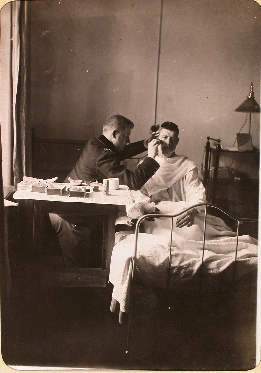 21. Студенты Политехнического института бреет раненого солдата в одной из палат госпиталя, оборудованного в здании института.