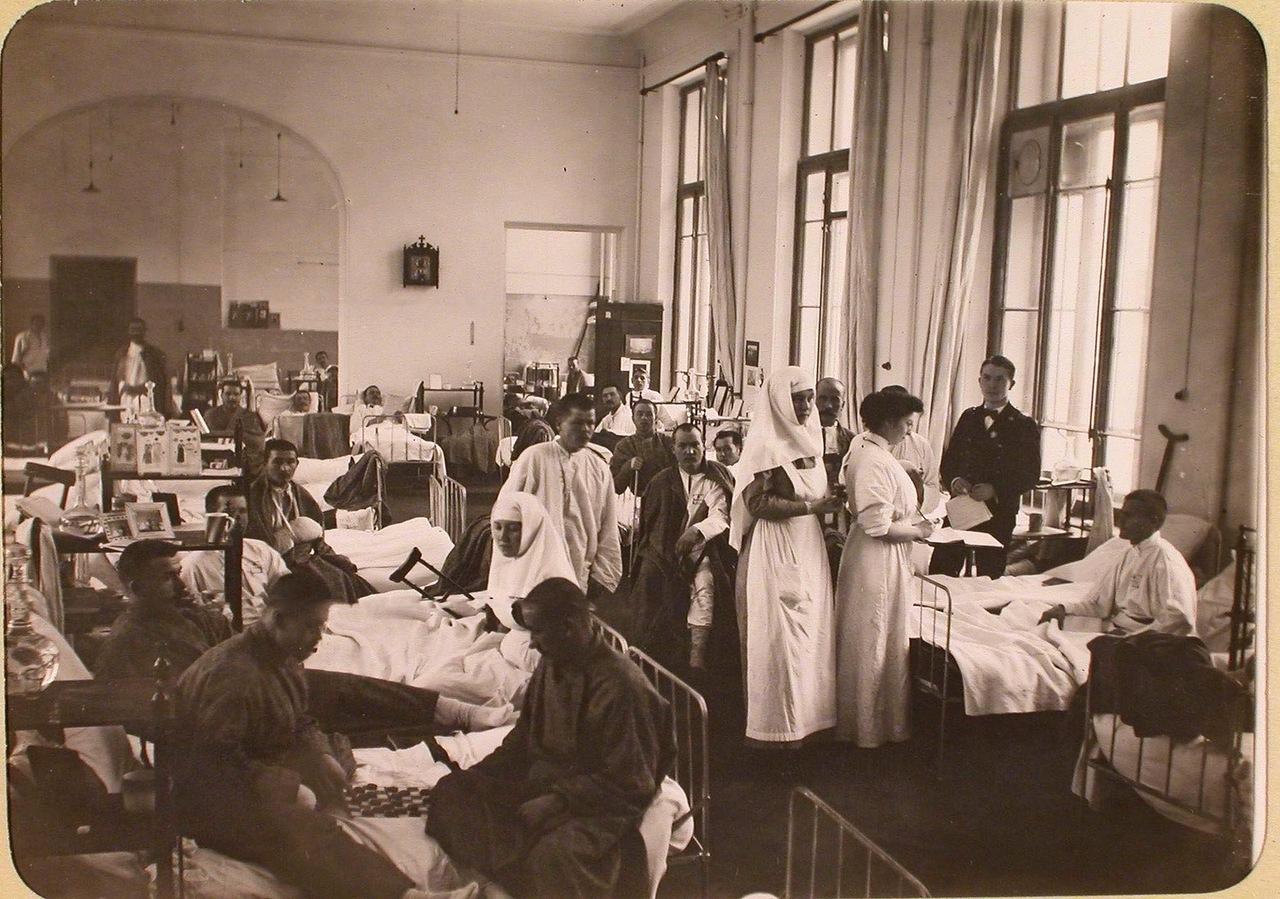 11. Женщина-врач и медицинская сестра во время обхода в одной из палат госпиталя, оборудованного в здании Политехнического института.