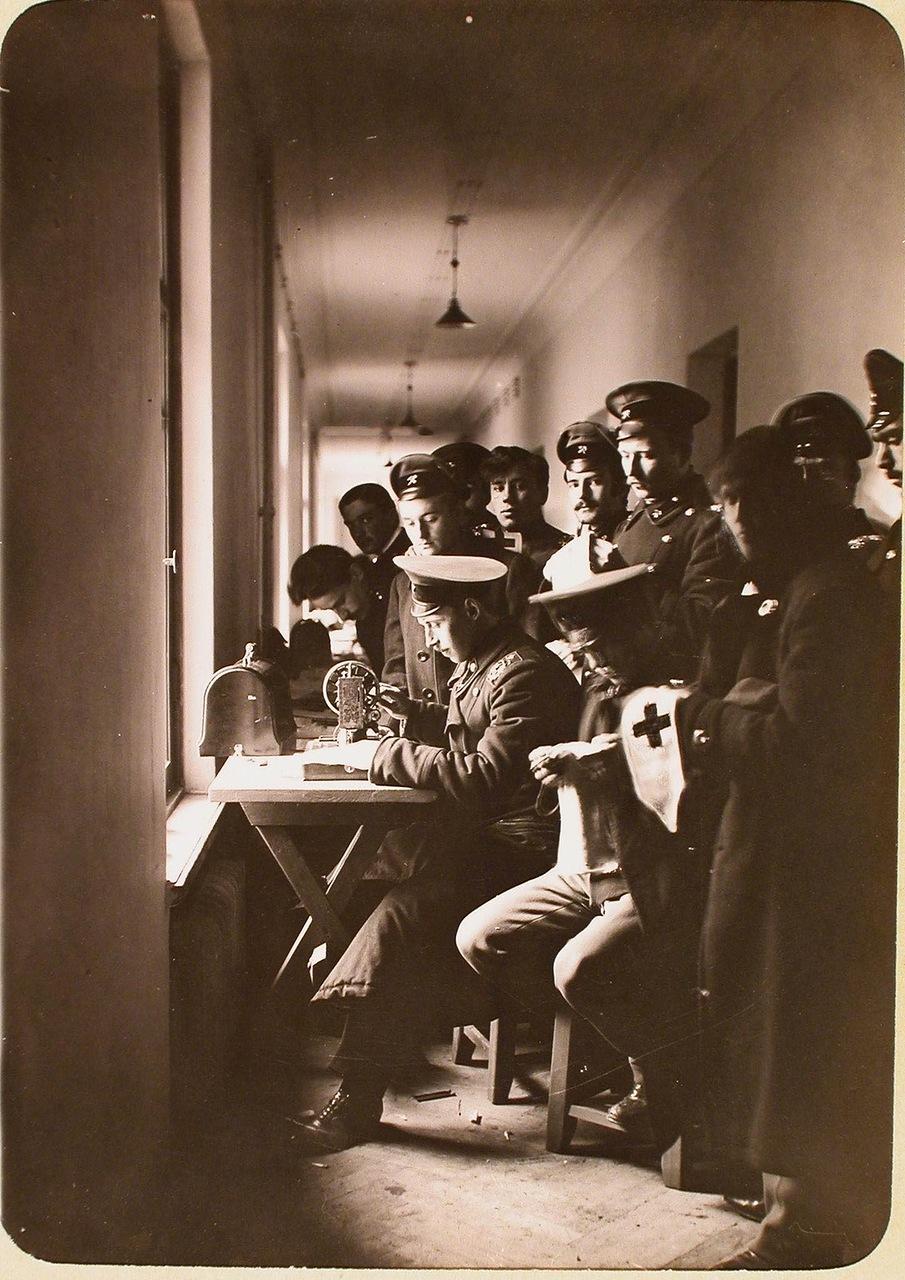 Студенты Политехнического института за шитьем повязок с Красным Крестом на ручной швейной машинке