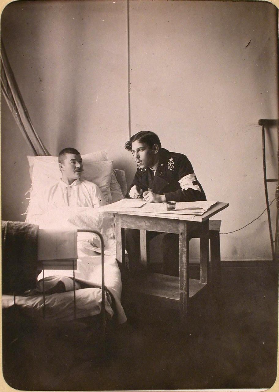 17. Студент Политехнического института пишет письмо под диктовку раненого солдата в одной из палат госпиталя, оборудованного в здании института.