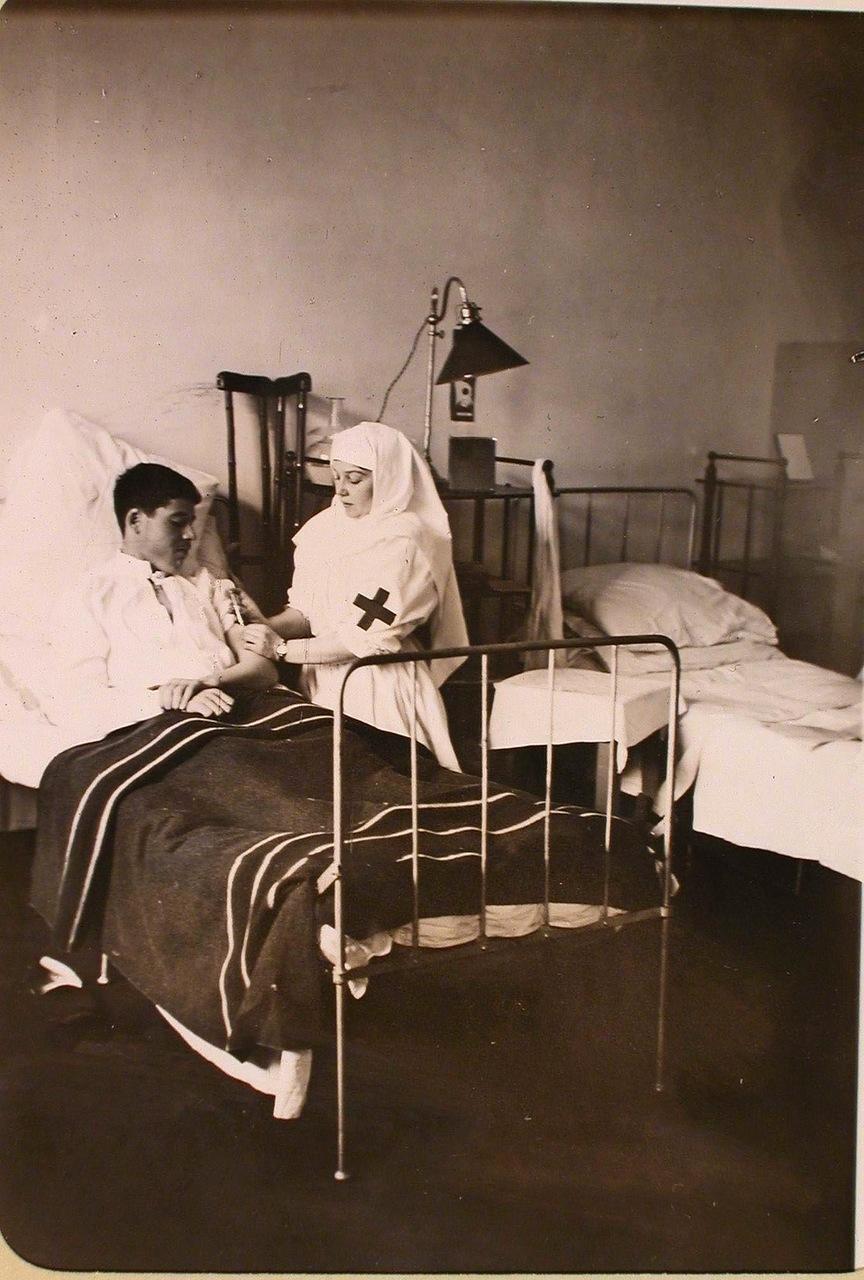 09. Медицинская сестра делает укол раненому в одной из палат госпиталя, оборудованного в здании Политехнического института.