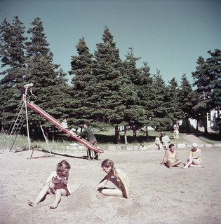 Two young girls play in the sand on a beach / Deux fillettes jouant dans le sable sur une plage