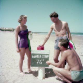 Two men and a woman chalking up the water temperature at Brackley Beach, Prince Edward Island National Park / Deux hommes et une femme traçant à la craie la température de l'eau à Brackley Beach, parc national de l'Île-du-Prince-Édouard