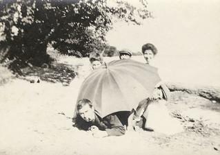 Group of people at the beach with an umbrella / Groupe de personnes avec une ombrelle à la plage