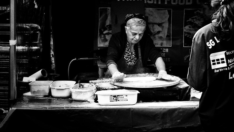 A woman rolls out a pizza base on a food stall in London's Brick Lane