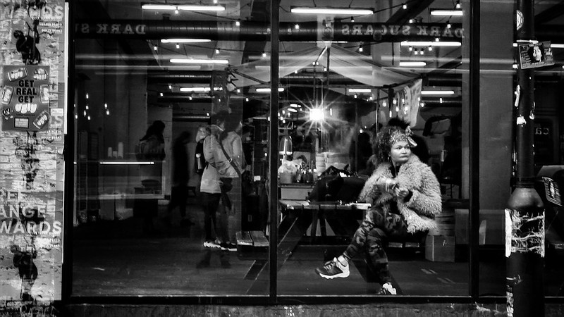 A woman sits inside the Sunday Up Market in London's Brick Lane, gazing outside