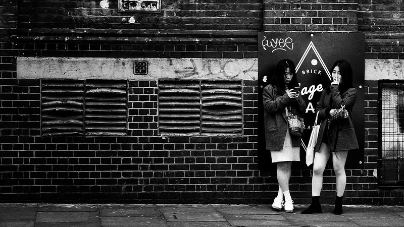 Two young women wait by a wall in London's Brick Lane